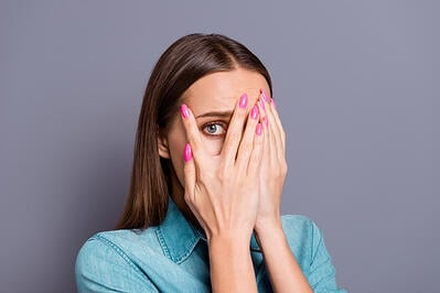 Woman with hands in front of face peaking out between fingers looking embarrassed about pregnancy incontinence