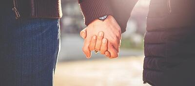 Couple going through fertility testing holding hands