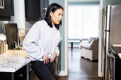 woman standing in kitchen looking troubled with hands on pelvic area and legs slightly crossed. Experiencing incontinence issues after pregnancy