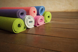 colorful yoga mats piled up, used for relieving pain from menstrual cramps