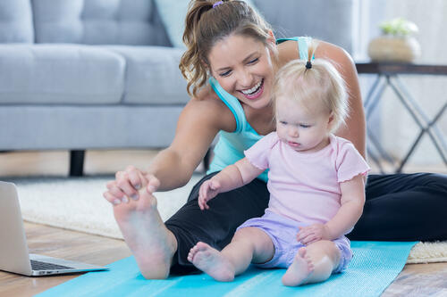Woman exercising after delivering her baby sitting next to her as she stretches on a yoga mat.