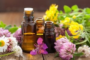bottles of essential oils that are safe for pregnancy surrounded by flowers